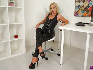 Despondent mistress in latex Jamie T is playing close to her smooth pussy